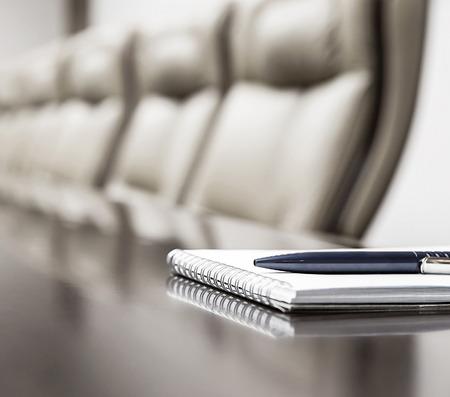 Nahaufnahme der Notizblock gehalten auf Tabelle im leeren Konferenzraum