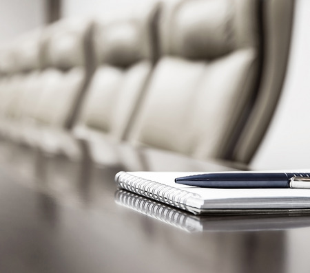 Closeup of notepad kept on table in empty conference room
