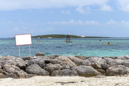 no swimming sign: Empty sign on rocks on Bahamas islands Stock Photo