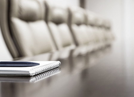 Closeup of notepad kept on table in empty conference room photo