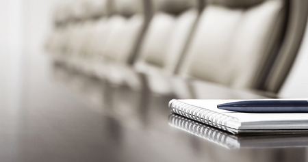 Closeup of notepad kept on table in empty conference room Stock Photo - 33545471