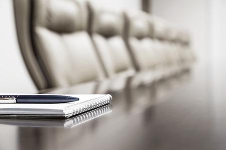 reunion de trabajo: Primer de la libreta mantuvo en la mesa en la sala de conferencias vacía