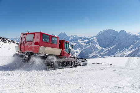 high up: Snowcat on a slope high up in the mountains Stock Photo