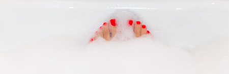 hot girl legs: Feet with red nails soaking in spa bath with copy space
