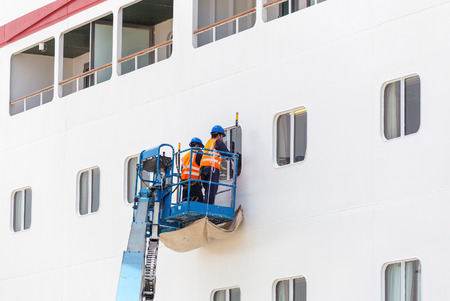 lifeboats: Workers cleaning windows on cruise ship in port