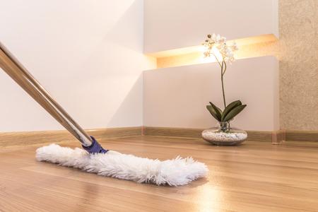 dweilen: Moderne witte mop schoonmaken van houten vloer in huis Stockfoto