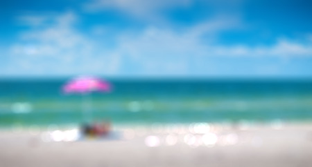 st  pete: Girl sunbathing under pink umbrella on St. Pete beach in Florida, USA, Blurred background