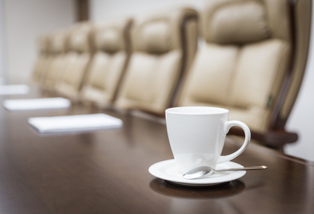 coffee meeting: Closeup of  on table in empty corporate conference room before business meeting in office