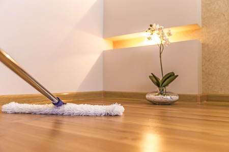 brooming: Modern white mop cleaning wooden floor in house
