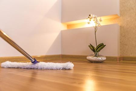 Moderne witte mop schoonmaken van houten vloer in huis Stockfoto