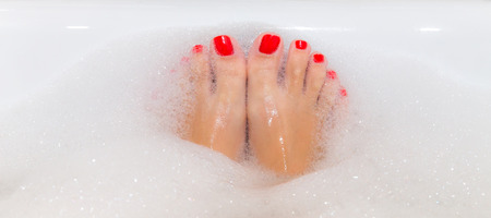 woman bath: Feet with red nails soaking in spa bath with copy space