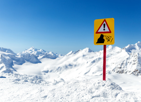 warns: Warning sign in  beautiful mountain landscape. Sign warns about the risk of falling Stock Photo