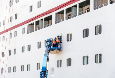 Workers cleaning windows on cruise ship in port