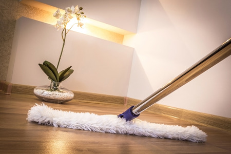 house maid: Modern white mop cleaning wooden floor in house