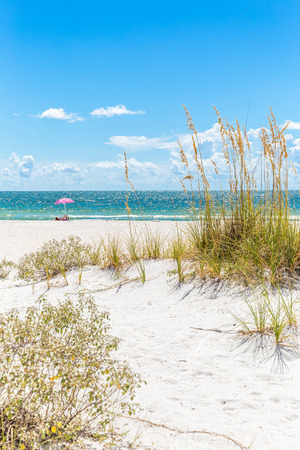 florida landscape: Girl sunbathing under pink umbrella on St. Pete beach in Florida, USA Stock Photo