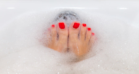 painted toes: Feet with red nails soaking in spa bath with copy space