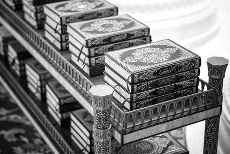 coran: holy Quran books on a shelf in a mosque, black and white Stock Photo