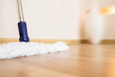 brooming: Modern white mop cleaning wooden floor from dust