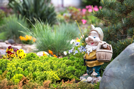 Funny garden gnome standing among nice flowers