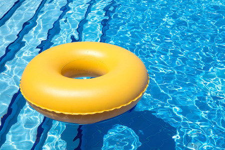 inner tube: inflatable yellow inner tube floating in clear blue waters