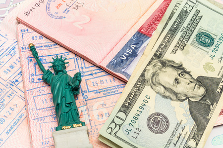 Passport, money and small statue of liberty