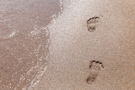 feet in water: Footprints in the sand