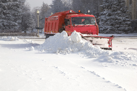 heap of snow: Snowplow removing snow from city road