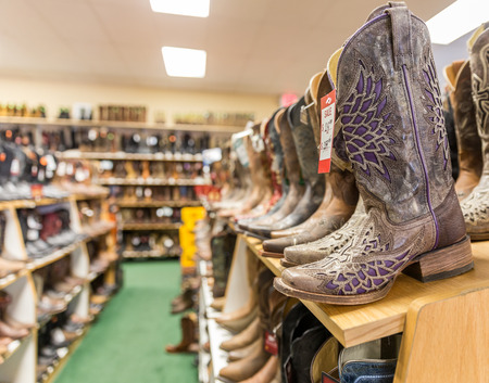 barn boots: LOS ANGELES, CALIFORNIA, USA - MAY 20, 2015 -  Close-up of new cowboy boots on shelf in Boot Barn store