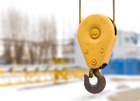 Yellow constraction crane hook with some industrial buildings on the background