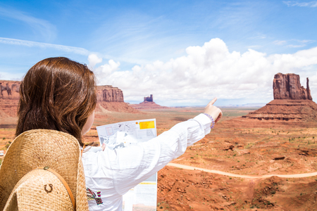 Back side of girl wearing straw hat searching right direction on map in Monument Valley, Utah, USA Stock Photo