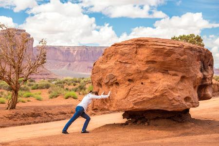 Chica empujando piedra, cocept imposible