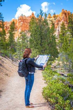 Girl  searching right direction on map in Bryce Canyon, USA Stock Photo