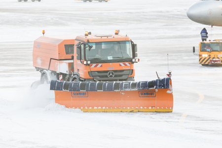 runways: MOSCOW, RUSSIA - DECEMBER 06, 2016 : Snowplow removing snow from runways and roads in airport during snow storm in SHEREMETYEVO airport on December 06.2016 in Moscow. Stock Photo