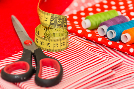 Measuring tape and scissors on red textile