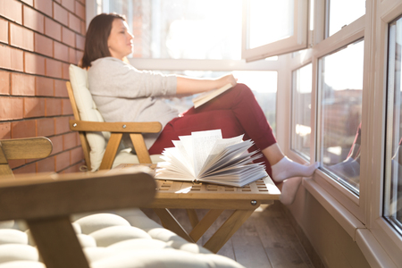 woman reading on balcony on a warm sunny day