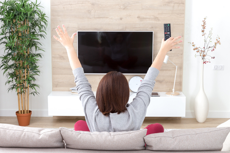 young happy woman watching excited television football sport match or TV contest Banco de Imagens