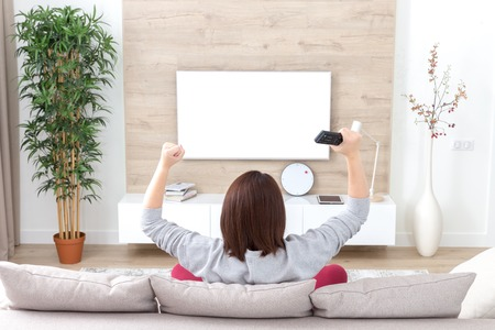 young happy woman watching excited television football sport match or TV contest Imagens