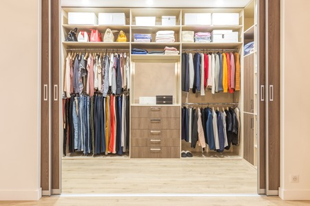 Armario de madera moderno con ropa colgada en el carril en el vestidor