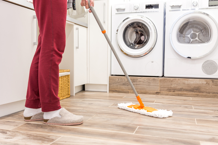 Cleaning floor in laundry room in modern house