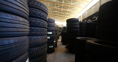 Piles of new tires in tyre warehouse in car garage
