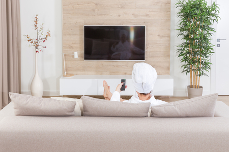Woman sitting on a couch with towel on her head watching tv Standard-Bild