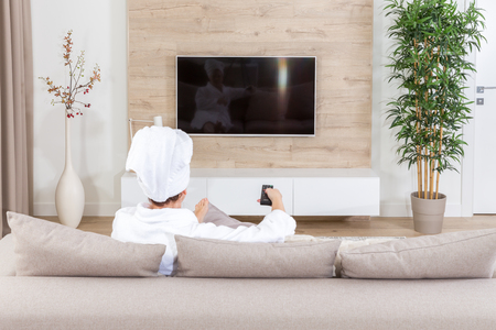 Woman sitting on a couch with towel on her head watching tv Stockfoto