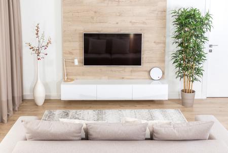 Salon z kanapą i telewizorem led na drewnianej ścianie