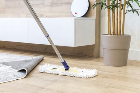 Piso de madera con fregona blanca, concepto de servicio de limpieza