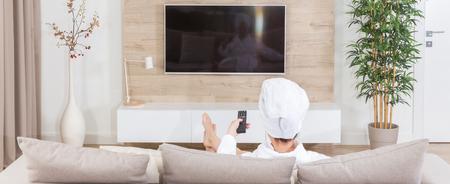 Mujer sentada en un sofá con una toalla en la cabeza viendo la televisión