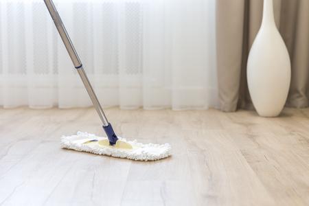 Vloer schoonmaken met witte dweil bij bank