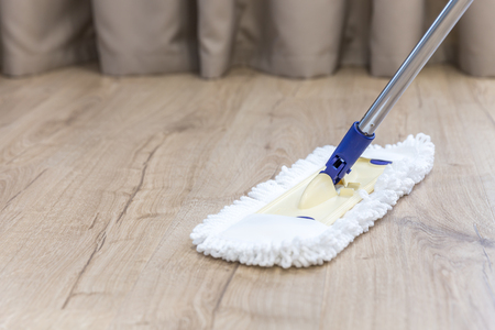 Modern white mop cleaning a wooden floor