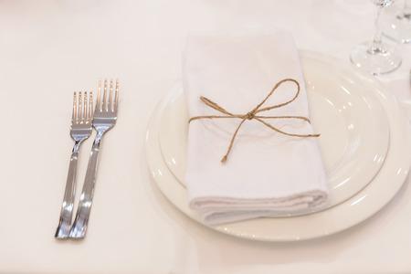 Plato, tenedores, servilleta y cuchillo en restaurante.