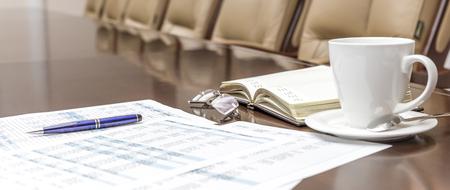 Primer plano de una taza de café con leche en la mesa en la sala de conferencias corporativa vacía