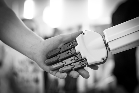 Man and robot handshake in a crowd. Concept of human interaction with artificial intelligence Stok Fotoğraf